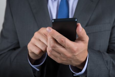 Close up of business man hands holding mobile phone