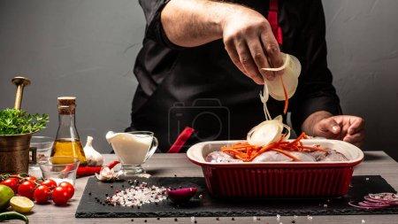 Photo pour Chef verser des légumes hachés sur la viande de lapin, processus de cuisson, Mains d'un chef préparant un lapin sauvage, recette pour la cuisson de la viande de lapin, Contexte de la recette alimentaire. espace pour le texte. - image libre de droit