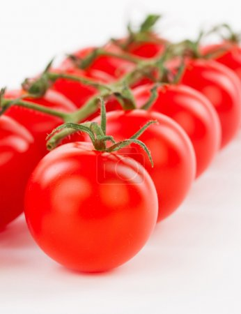 Juicy organic Cherry tomatoes with green leaf isolated over whit