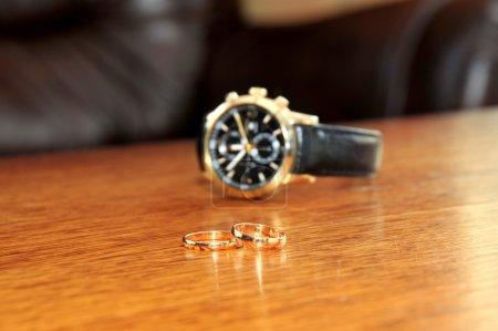 Photo pour Bague de mariage et montres homme sur la table en bois - image libre de droit