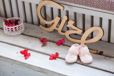 Sweet fancy and colorful baby shoes on the wooden desk with girl