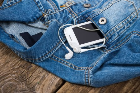 Headphones and smartphone in the pocket old denim jacket