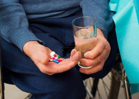 Photo pour Homme handicapé âgé prenant des médicaments quotidiens . - image libre de droit