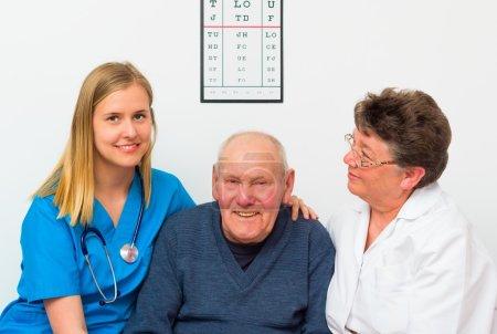 Photo pour Heureux homme âgé soutenu par son médecin et son infirmière . - image libre de droit