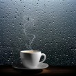 Steaming coffee cup on a rainy day window backgrou...