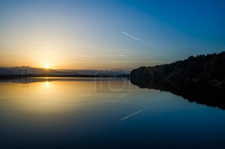 Lake sunset view with jet plane trail