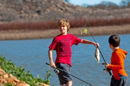 Two boys on catching a fish.