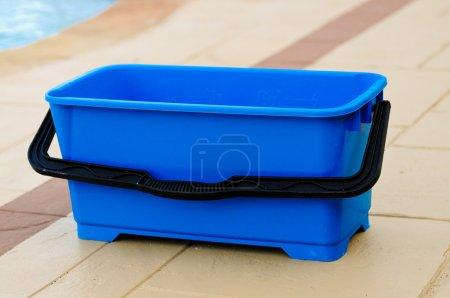 Photo pour Seau bleu vide à l'extérieur sur le patio en béton estampé. - image libre de droit