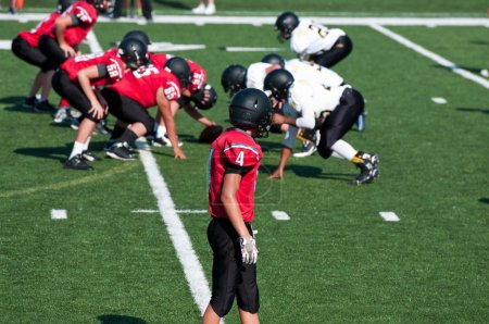 Photo for High School American football receiver waiting for play to start during the game. - Royalty Free Image