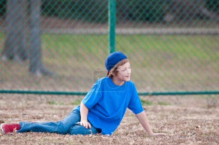 Young boy with baseball cap laying in grass