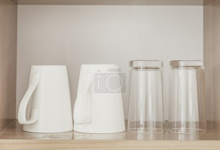 Photo for White coffee cups and empty glasses in kitchen cabinet - Royalty Free Image