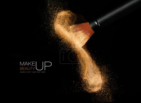 Photo for Soft cosmetics brush releasing a cloud of glowing sparkling face powder over a black background with copy space in a beauty and makeup concept - Royalty Free Image