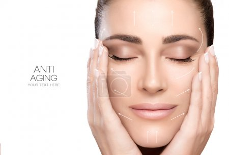 Photo for Anti aging treatment and plastic surgery concept. Beautiful young woman with hands on cheeks and eyes closed with a serene expression and white arrows over face. Perfect skin. Portrait isolated on white with copy space for text. - Royalty Free Image