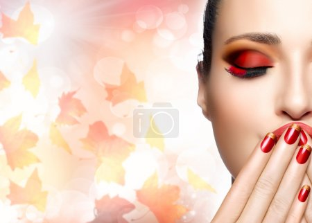 Photo for Autumn makeup and nail art trend. Fall beauty fashion girl. Professional makeup and manicure. Closeup portrait of half face on autumnal background with falling leaves - Royalty Free Image