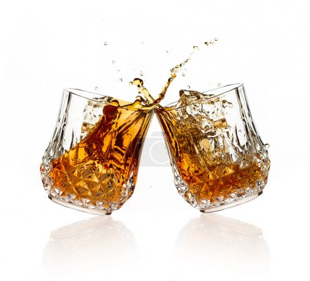 Photo for Cheers. A Toast with whiskey. Two glasses clicking together over white background. Splashing whisky on glasses of cut glass - Royalty Free Image