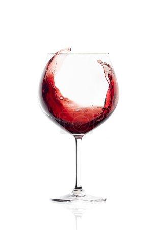 Photo pour Vin rouge dans un verre à ballon. Splash. Lunettes isolées sur fond blanc - image libre de droit