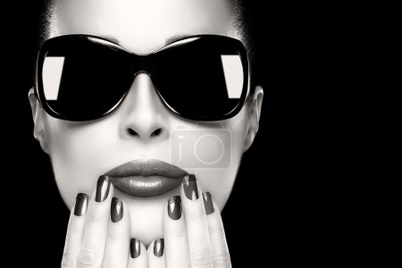 Photo for Beautiful fashion model girl with stylish oversized black sunglasses. Bright makeup and manicure. High fashion portrait in black and white isolated on black with copy space for text. Fashion beauty and nail art concept. - Royalty Free Image