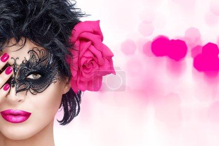 Foto de Bellezas de modelo con máscara de carnaval con estilo de negro y flor grande rosa. Manicura y labios rosados. Belleza glamour modelo usa maquillaje disfraces creativos. Closeup retrato sobre fondo rosa bokeh con espacio de copia de texto. - Imagen libre de derechos