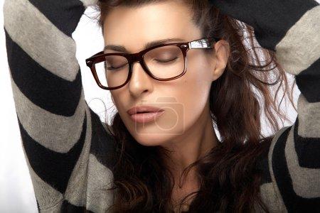 Photo pour Gros plan magnifique fille modèle de mode brune avec des vêtements de style décontracté portant des lunettes à la mode, tenant ses cheveux les yeux fermés. Cool tendance lunettes portrait isolé sur fond blanc - image libre de droit
