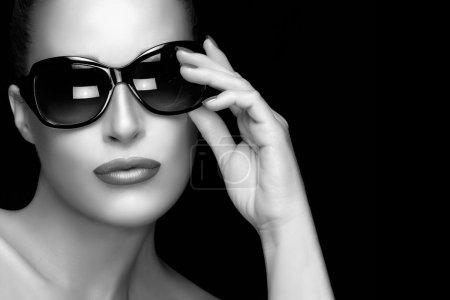 Photo pour Belle fille modèle de mode avec main sur ses lunettes de soleil surdimensionnées élégantes regardant la caméra. Maquillage professionnel et manucure. Portrait noir et blanc haute couture sur fond noir avec espace de copie. Concept beauté et mode . - image libre de droit