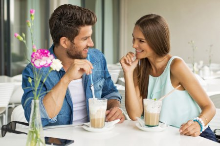 Smiling couple in cafe enjoying the time spending with each othe