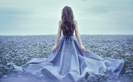 Photo for Back view of standing young woman in blue dress on the floral field - Royalty Free Image