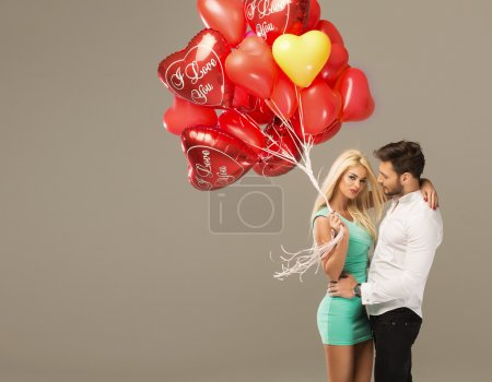 Photo for Happy loving couple with red heart balloons on grey background - Royalty Free Image