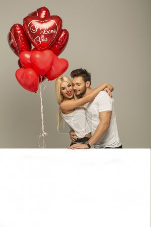 Young couple with red balloons