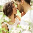 Portrait of kissing couple in the blooming garden...