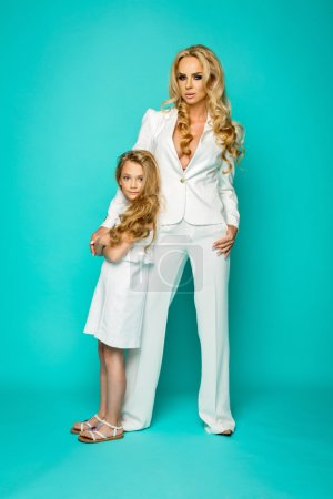 Photo for Fashion woman and little girl standing in white clothes on blue background - Royalty Free Image