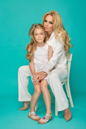 Photo for Fashion woman and pretty little girl sitting on chair on blue background - Royalty Free Image