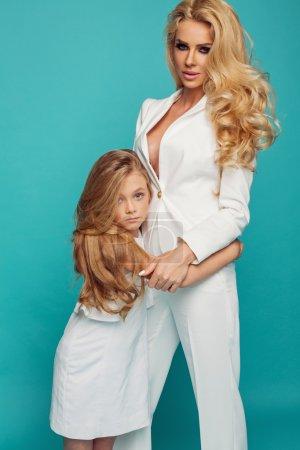 Photo pour Photo de mode de la belle mère et sa fille dans des vêtements blancs sur fond turquoise - image libre de droit
