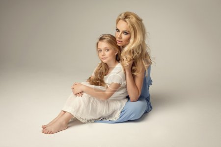 Photo for Beautiful mother and daughter posing in studio, sitting on floor - Royalty Free Image