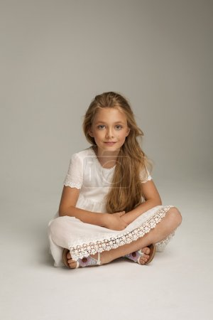 Photo for Smiling little girl sitting on floor in studio with hand on chin - Royalty Free Image
