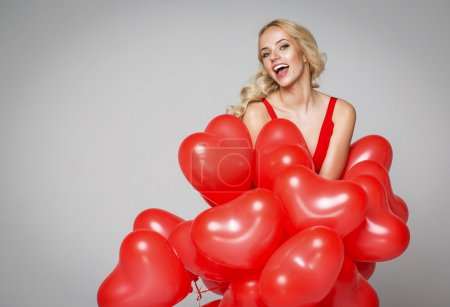 Beautiful smiling blond woman posing and holding balloons