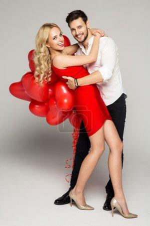 Photo pour Joyeux beau couple posant sur fond gris et tenant des ballons - image libre de droit