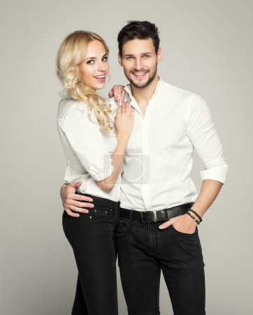 Fashionable couple in white shirts, posing on grey background