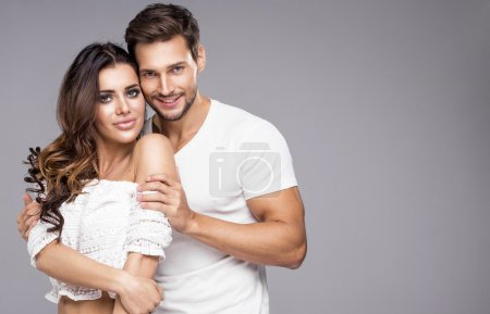 Photo pour Beau jeune couple posant sur fond gris - image libre de droit