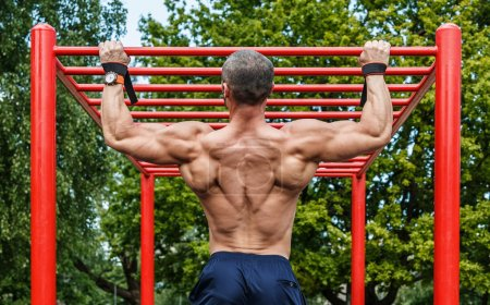 Man doing pull-ups on horizontal bar