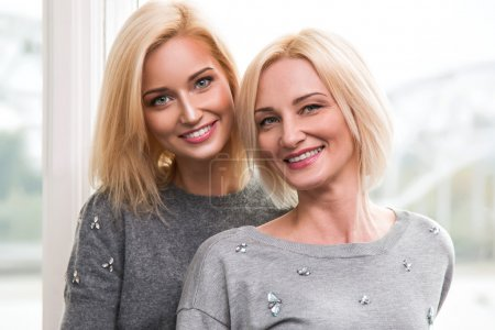 Beautiful smiling blond mother and daughter...