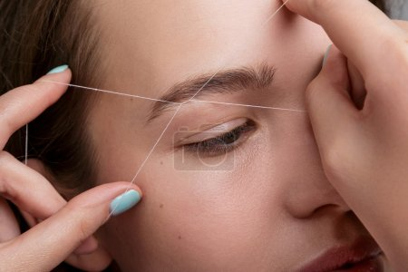 Close-up of female face during eyebrow correction ...