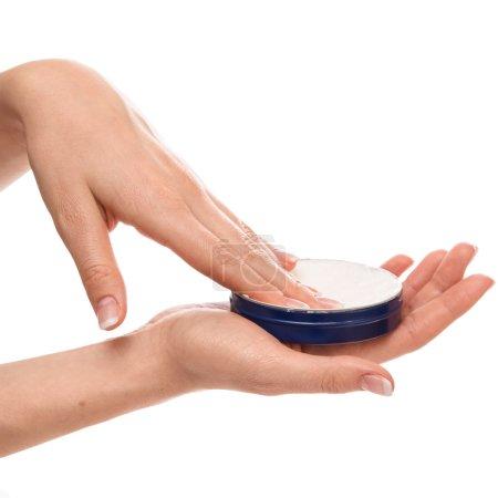 Woman applying moisturizer cream on hands