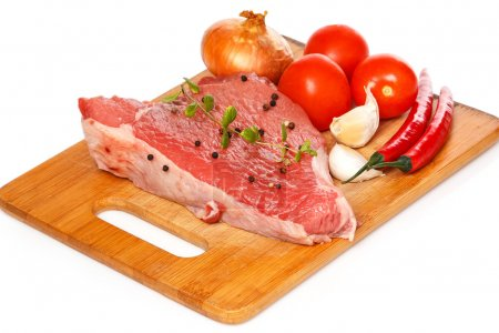 Photo for Raw meat and vegetables on chopping board - Royalty Free Image