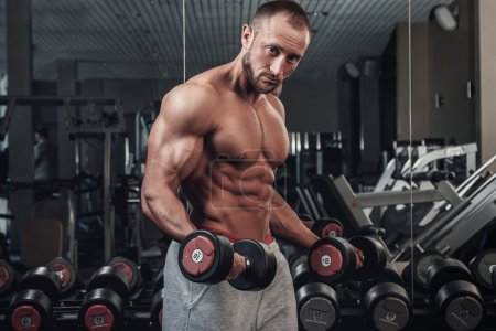 Photo for Young and muscular man doing a exercise for biceps - Royalty Free Image