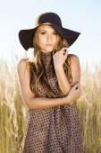 Krásná mladá dáma model představuje před kamerou v poli při východu slunce