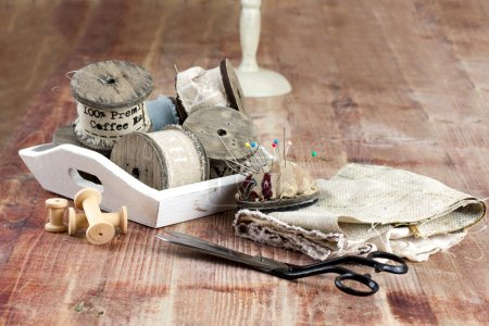 Old spools of thread, fabric, scissors on a wooden background