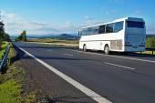 Bílý autobus na prázdné silnici ve venkovské krajině