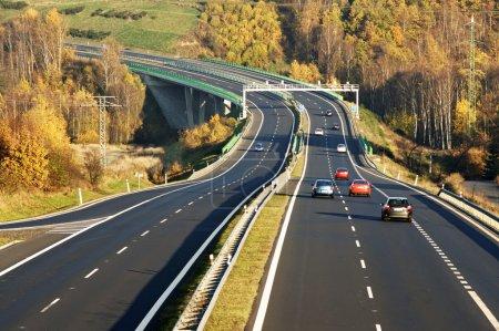 Photo pour Voitures sur l'autoroute menant à travers le pont au-dessus de la vallée, barrières de péage électroniques, forêt de feuillus dans les couleurs d'automne, vue d'en haut - image libre de droit