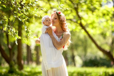 Beautiful mother in long dress is standing in the park or forest  and  her little baby girl daughter on her hands hugging her