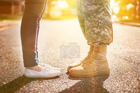 Young military couple kissing each other, homecomi...